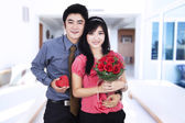 Attractive couple holds a gift and flowers — Stock Photo