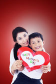 Asian mother and son holding love card on red — Stockfoto