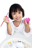 Cute little girl coloring an easter egg — Stock Photo