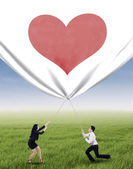 Business people pulling valentine banner — Stock Photo