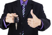 Businessman offering a car key with thumbs-up — Stock Photo