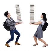 Young couple carrying a pile of books — Stock Photo