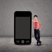 Businessman and smartphone on grey — Stock Photo