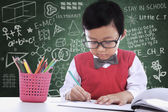 Asian student boy writing on paper in class — Photo