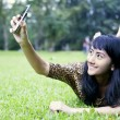 Stock Photo: Asian woman taking picture with mobile phone at the park