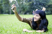 Asian woman taking picture with mobile phone at the park — Stock Photo