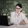 Beautiful doctor writes formula — Stock Photo