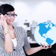 Businesswoman calling and holding a globe — Stock Photo