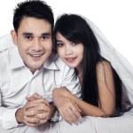 Happy couple hiding under blanket — Stock Photo