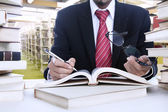 Businessman taking notes at library — Stok fotoğraf