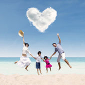 Happy family jumping under love cloud at beach — Stock Photo