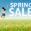 Stock Photo: Girl jumping with spring sale clouds