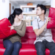 Stock Photo: Angry couple on red sofa at home