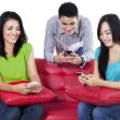 Stock Photo: Three teenagers typing sms