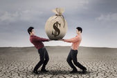 Businessmen carrying a sackful money — Stock Photo
