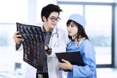 Doctors with patient xray film — Stock Photo