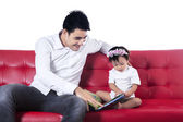 Happy family reading story book on sofa — Stock Photo