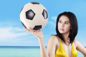 Sexy model holding soccer ball at beach — Stock fotografie