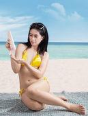 Woman putting on sunscreen — Stock Photo