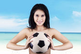 Woman smiling while holding soccer ball — Stock fotografie