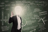 Businessman with lightbulb head in classroom — Stock Photo