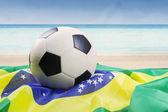 Pallone da calcio sopra la bandiera brasiliana — Foto Stock