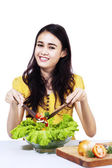 Young housewife mixing vegetable salad — Stock Photo