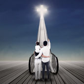 Family looking at bright cross — Stock Photo