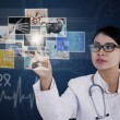 Female doctor touching photos on blue touchscreen — Stock Photo #45306275
