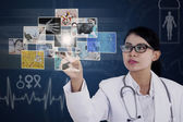 Female doctor touching photos on blue touchscreen — Stock Photo