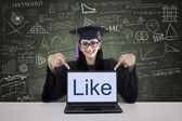 Graduation student showing like on laptop shot in class — Stock Photo