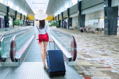 Young woman with a suitcase on the airport — Stock Photo
