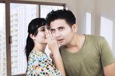 Beautiful woman whispering to boyfriend's ear — Stockfoto