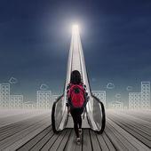 College student stepping upward on escalator 1 — Stockfoto