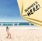 Happy woman pulling a summertime banner — Stock Photo