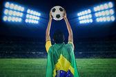 Brasilianska supporter håller en boll på fältet — Stockfoto