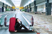 Businesswoman sitting on the floor in airport — Stock Photo
