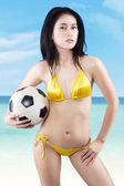 Sexy woman wearing bikini holding a soccer ball — Foto de Stock
