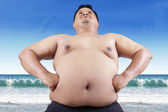 Fat man with big stomach on beach — Stock Photo