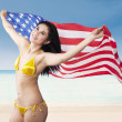 Sexy woman holding american flag at beach — Stock Photo