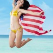 Sexy woman jumping with holding american flag — Stock Photo