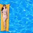 Woman floating on a pool mattress — Stock Photo
