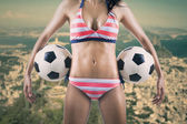 Sexy soccer fan holding two balls — Stock Photo