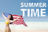 Woman holding american flag enjoying summertime — Stock Photo