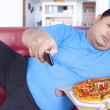Obese man holds pizza and remote 1 — Stock Photo