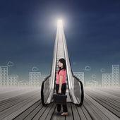 Businesswoman standing on the escalator — Stock Photo