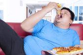 Obese person bite a slice of pizza — Stock Photo