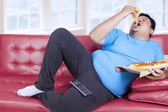 Overweight man eats pizza — Stock Photo