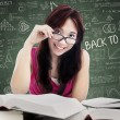 Beautiful female college student in class — Stock Photo #49862379