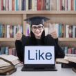 Female graduate thumbs up in library — Stock Photo #49866627